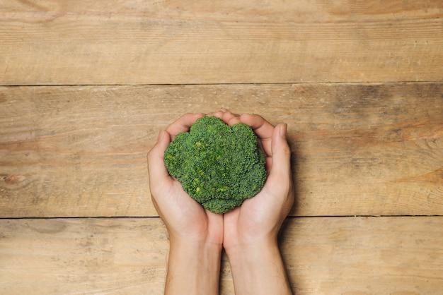 Verse broccoli in handen op een houten achtergrond