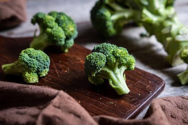 Verse broccoli met houten snijplank op oude houten tafel