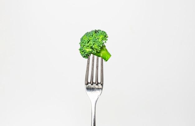 Verse broccoli op vork die op wit wordt geïsoleerd. gezonde levensstijl