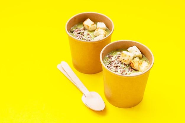 Verse broccolisoep met croutons en zaden in ambachtelijke containers