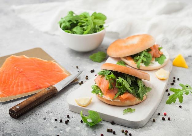 Verse broodjes met bagel en zalm, roomkaas en wilde raket op wit bord met gerookte zalm pack en mes op lichte achtergrond.