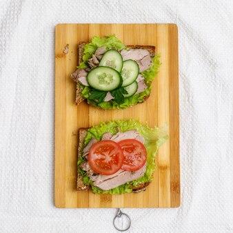 Verse broodjes met gebakken vlees en groenten op houten snijplank, bovenaanzicht