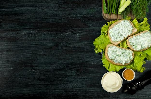 Verse broodjes met groenten op een donker bord