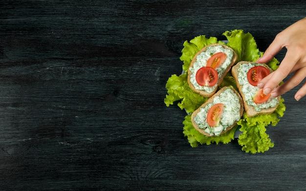 Verse broodjes met groenten op een donkere bord op een gestructureerde ondergrond.