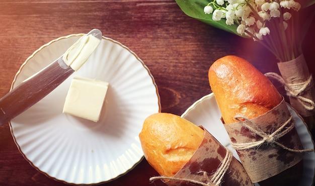 Verse broodjes voor het ontbijt. broodje met boter tot een kopje koffie in de ochtend. ontbijt in het hotel broodjes jam thee en een boeket bloemen.