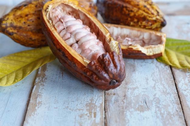 Verse cacaopeulen en cacaobladeren op houten oppervlak