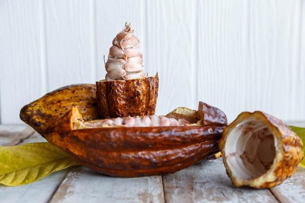 Verse cacaopeulen en cacaobladeren op houten tafel