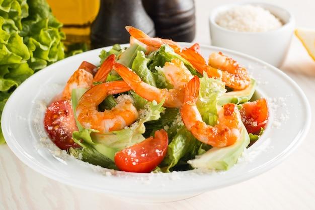 Verse caesar-garnalensalade met heerlijke garnalen, rucola, spinazie, kool, rucola, ei, parmezaanse kaas en kersentomaat gezond en dieetvoedselconcept.
