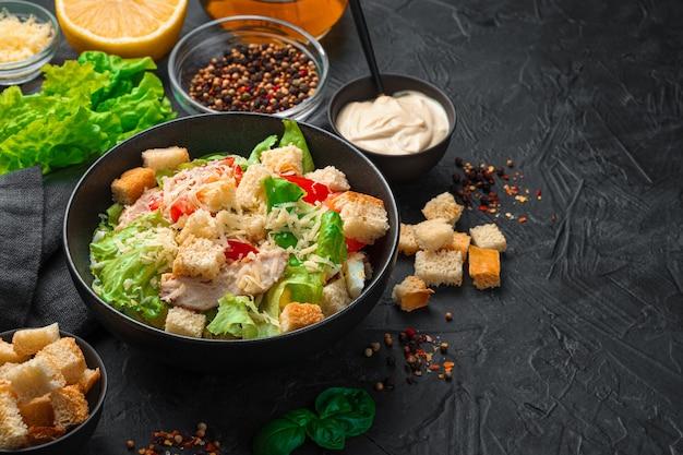 Verse caesarsalade met saus, crackers en kruiden op een zwarte achtergrond. koken concept.