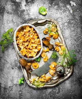 Verse cantharellen champignons met kruiden en een oud mes op een stalen dienblad op een rustieke tafel.