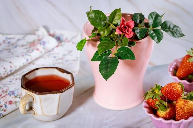 Verse carkadethee met aardbei en vaas met roos.