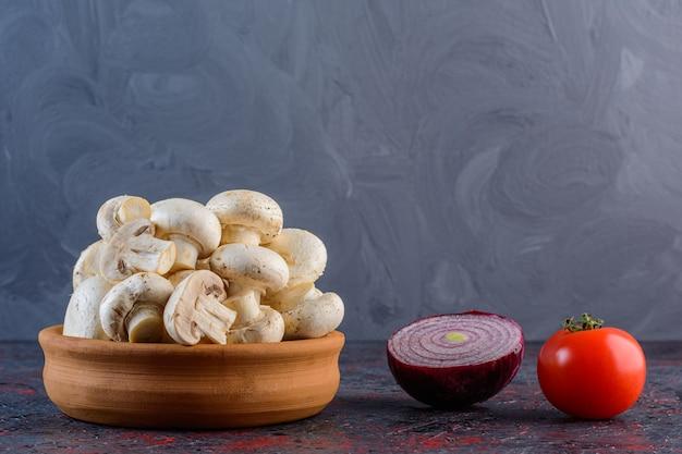Verse champignonpaddestoelen met rode tomaat en paarse ui op een donkere ondergrond