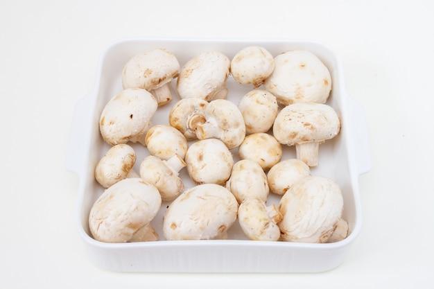 Verse champignons in een witte ceramische ovenschaal