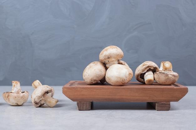 Verse champignons op houten plaat.