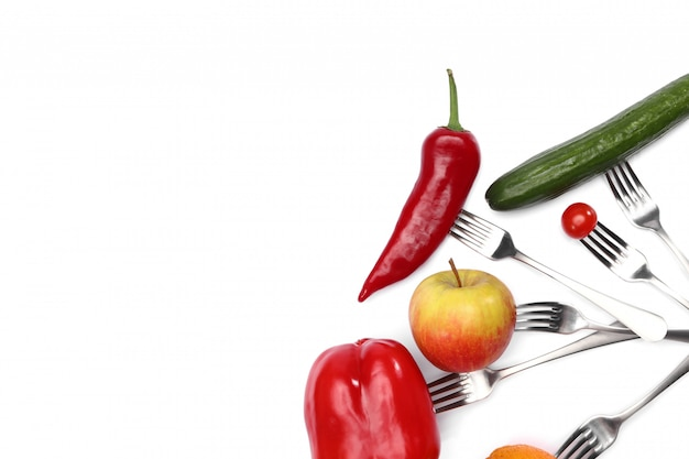 Verse cherry tomaten, rode paprika, komkommer, appel en oranje vruchten op vorken op wit.