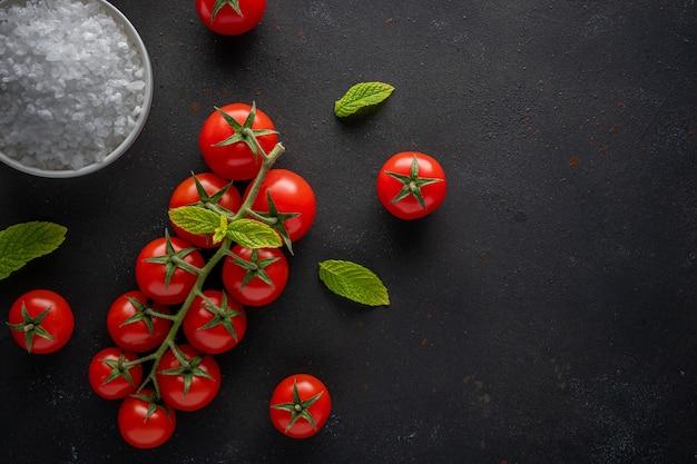 Verse cherrytomaatjes op een zwarte met kruiden.