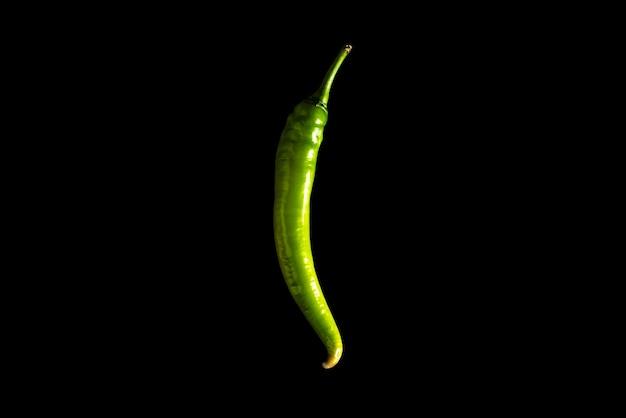 Verse chilipeper van groene kleur ligt op een zwarte achtergrond.