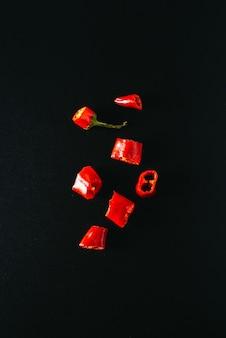 Verse chilipepers, in stukjes gesneden, liggen op een zwarte achtergrond.
