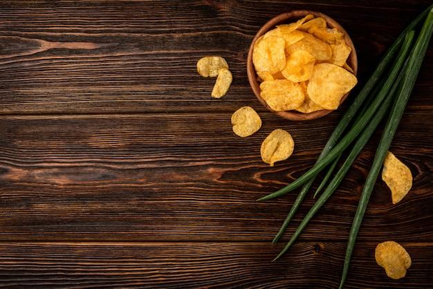 Verse chips met groene ui op een houten tafel