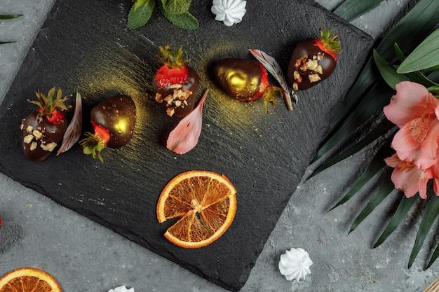 Verse chocolade bedekt aardbeien op een grijze decoratieve achtergrond. concept voor het adverteren van het zomerse seizoensmenu.