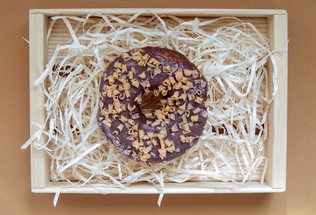 Verse chocolade donut geïsoleerd op koffie achtergrond. heerlijk dessert met glanzend chocoladeglazuur. zoet voedselconcept met één ronde chocoladedoughnut voor uw ontwerp en bedrukking. bovenaanzicht, plat gelegd.