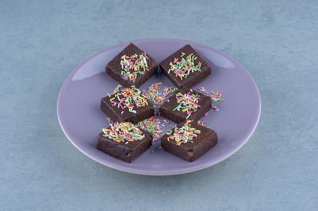 Verse chocoladewafels op paarse plaat over grijs.