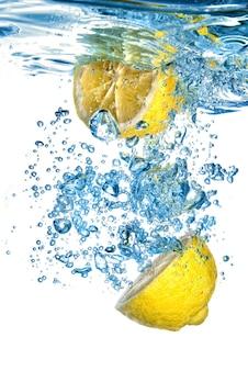 Verse citroen daalde in water met bellen die op wit worden geïsoleerd
