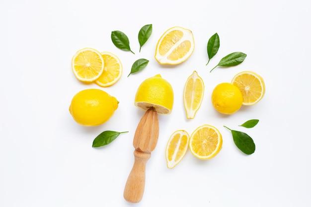 Verse citroen en bladeren met houten juicer op wit