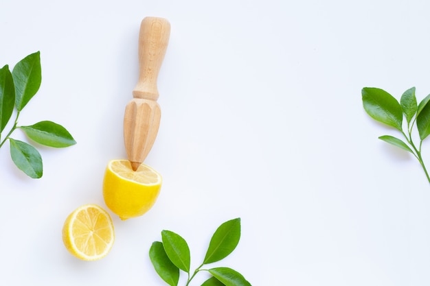 Verse citroen en bladeren met houten juicer op witte achtergrond.
