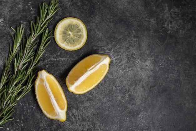 Verse citroen en rozemarijn op een donkere textuurachtergrond