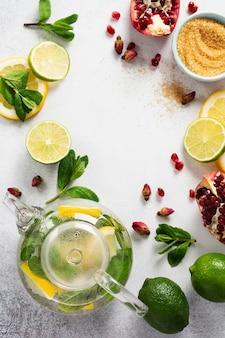 Verse citroen, limoen, granaatappel, gedroogde thee rozenbloemen, thee, rietsuiker, muntblaadjes en glazen theepot op grijze tafel