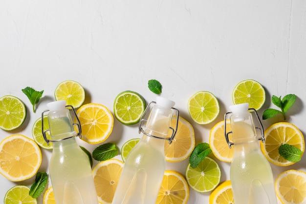 Verse citroen-limoen-muntdrank in glazen fles met ingrediënten zomerdrankje