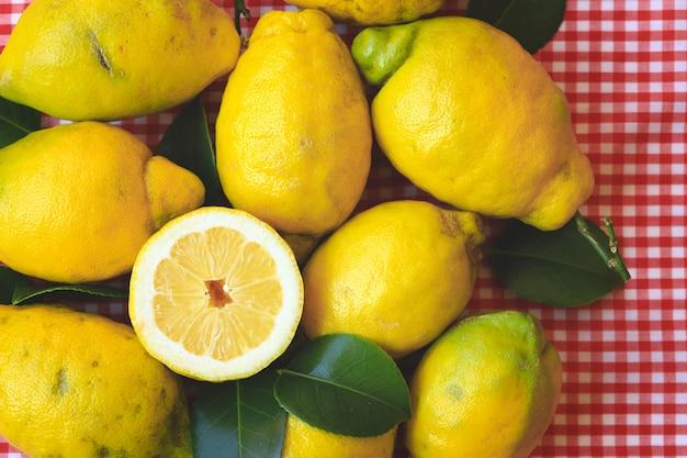Verse citroen met bladeren op rood tafellaken