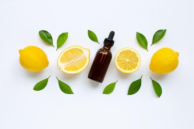 Verse citroen met citroenetherische olie op een wit.