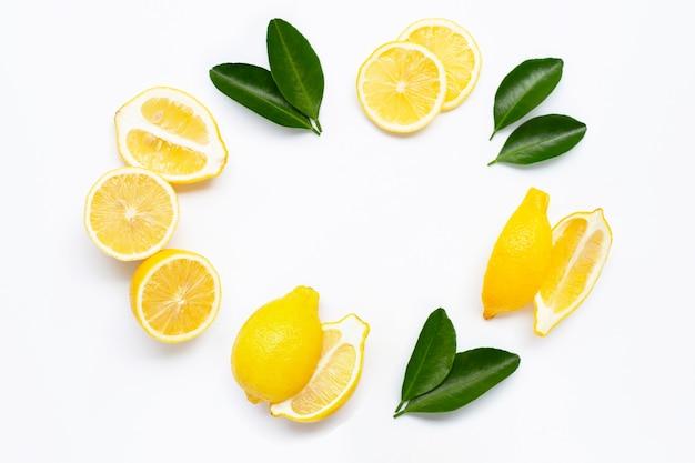 Verse citroen met groene bladeren op wit.