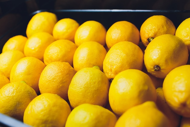 Verse citroenen in een houten doos. op het zwarte schoolbord.