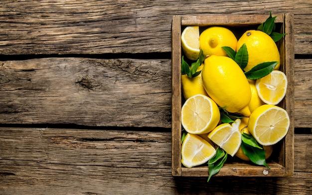 Verse citroenen in een oude doos met bladeren op houten tafel. bovenaanzicht