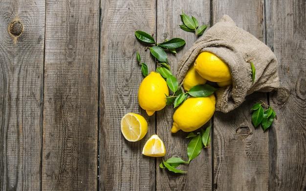 Verse citroenen in een oude zak met bladeren. op houten achtergrond. vrije ruimte voor tekst. bovenaanzicht