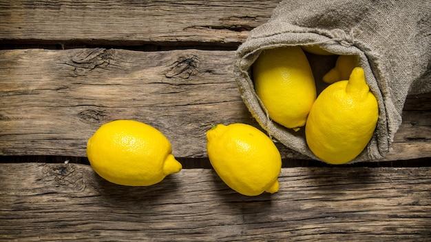 Verse citroenen in een oude zak. op een houten achtergrond. bovenaanzicht