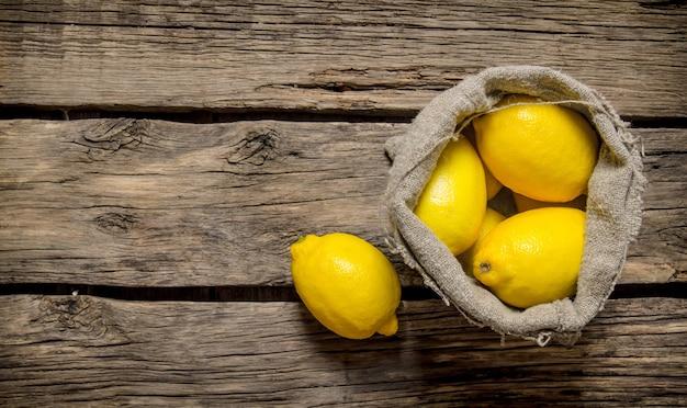 Verse citroenen in een oude zak. op een houten achtergrond. vrije ruimte voor tekst. bovenaanzicht