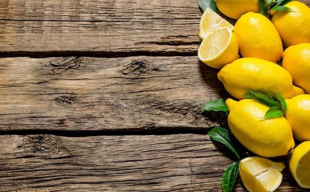 Verse citroenen met bladeren op houten tafel. bovenaanzicht