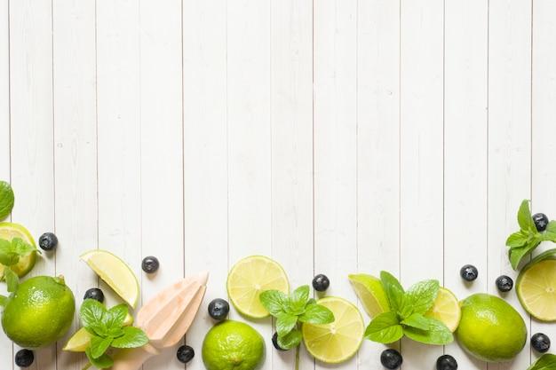 Verse citrusvruchten limoen munt bosbessen op een lichte achtergrond.