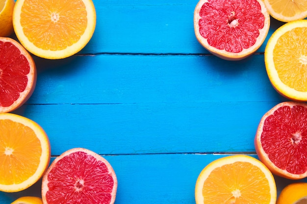 Verse citrusvruchten met groene bladeren op houten blauwe achtergrond