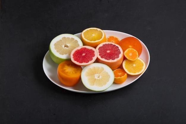 Verse citrusvruchten op witte schotel close-up, donkere achtergrond