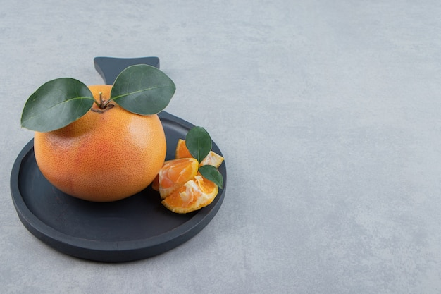 Verse clementine en segmenten op zwarte plaat.