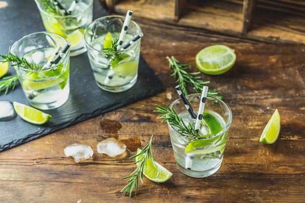 Verse cocktail met limoen, ijs en rozemarijn, mojitococktail in een bur op een rustieke tafel