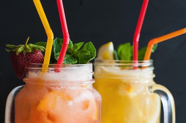 Verse cocktails in glazen pot op zwart voor het stillen van dorst.