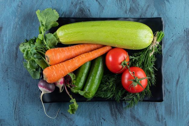 Verse courgette, wortel, tomaat en groenen op zwarte plaat.