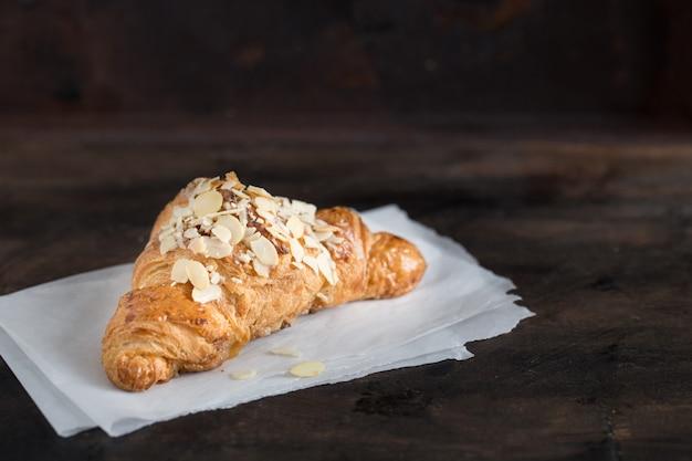 Verse croissant en koffie in een papieren kopje op donker