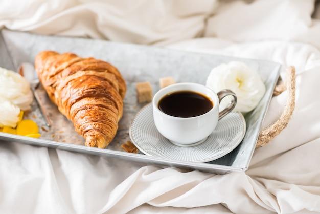 Verse croissant, kopje koffie en ranunculus bloemen voor het ontbijt